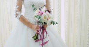 Het mooie bruids boeket in handen van jonge bruid kleedde zich in witte huwelijkskleding Sluit omhoog van grote bos van vers wit stock videobeelden