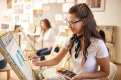 Het mooie bruin-haired meisje in glazen gekleed in witte t-shirt en jeans met een sjaal rond haar hals schildert een beeld royalty-vrije stock foto's