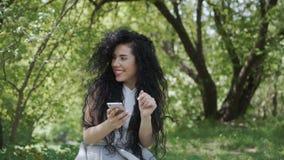 Het mooie brunette begroet met iemand in tuin wanneer zij ` s gebruikend haar telefoon stock videobeelden