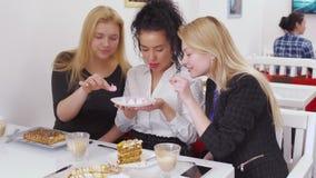 Het mooie brunette biedt haar vrienden smakelijke schuimgebakjes in koffie aan stock video