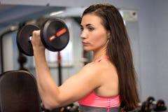 Het mooie brunette die in een gymnastiek uitwerken die zware hand opheffen weegt stock foto