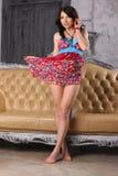 Het mooie brunette in een heldere kleding bevindt zich dichtbij een leerbank Royalty-vrije Stock Foto's
