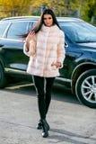 Het mooie brunette in een lichte bontjas en zwarte broeken bevindt zich op de straat voor de auto op de zonnige herfst stock foto's