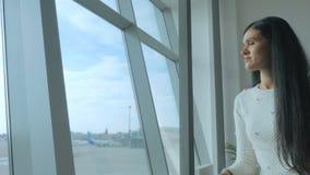 Het mooie brunette kijkt dreamily op de baan met vliegtuigen stock video