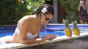 Het mooie brunette met een bloem in haar haar gebruikt een smartphone op de rand van het zwembad meisje in het witte baden stock videobeelden