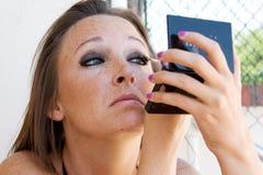 Het mooie brunette past oogschaduw toe. Stock Afbeelding