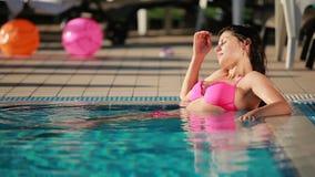 Het mooie brunette in roze zwempak zonnebaadt in het zwembad stock video