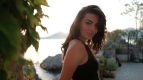 Het mooie brunette stelt in openlucht op overzeese kust op de zomeravond stock footage
