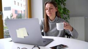 Het mooie bureau van de vrouwenzitting thuis en het werken aan laptop stock video