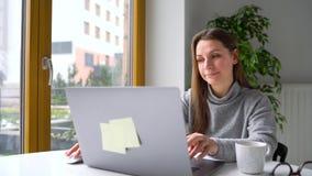 Het mooie bureau van de vrouwenzitting thuis en het werken aan laptop stock footage