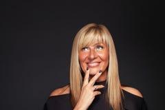 Het mooie dagdromen van de blonde rijpe vrouw Royalty-vrije Stock Foto's
