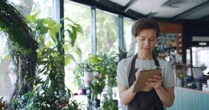 Het mooie dame tellen plant het schrijven gegevens in notitieboekje lopend in bloemwinkel stock video