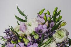 Het mooie de lenteboeket van huwelijk bloeit boterbloemenranunculus, fresia, lavendel in vaas met violette band pastelkleur Stock Afbeelding