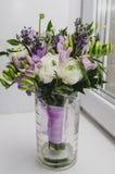 Het mooie de lenteboeket van huwelijk bloeit boterbloemenranunculus, fresia, lavendel in vaas met violette band pastelkleur Stock Afbeeldingen