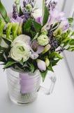 Het mooie de lenteboeket van huwelijk bloeit boterbloemenranunculus, fresia, lavendel in vaas met violette band pastelkleur Stock Foto