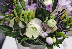 Het mooie de lenteboeket van huwelijk bloeit boterbloemenranunculus, fresia, lavendel in vaas met violette band pastelkleur Royalty-vrije Stock Foto's