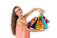 Het mooie die meisje in de handen van heldere gekleurde pakketten met giften wordt opgeheven is geïsoleerd op een witte achtergro Royalty-vrije Stock Fotografie