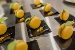 Het mooie dienen van makarons op zwarte die platen met bessen worden verfraaid stock afbeeldingen