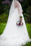 Het mooie donkerbruine bruid stellen in bloemweide met huwelijk BO Stock Fotografie