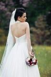 Het mooie donkerbruine bruid stellen in bloemweide met huwelijk BO Royalty-vrije Stock Foto