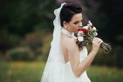 Het mooie donkerbruine bruid stellen in bloemweide met huwelijk BO Royalty-vrije Stock Afbeeldingen