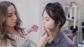 Het mooie donkerbruine meisje gebruikt de diensten van een professionele winkel van Beauty van de make-upkunstenaar Grimeur en ha stock video