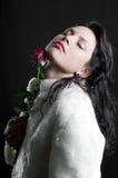 Het mooie donkerbruine meisje met rood nam ter beschikking toe Royalty-vrije Stock Fotografie