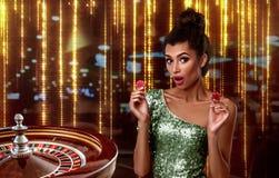 Het mooie donkerbruine meisje met spaanders bevindt zich op de achtergrond van een koninklijke roulette collage met een gokker, r stock afbeeldingen