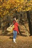 Het mooie donkerbruine meisje van de gitaarspeler in het bos Royalty-vrije Stock Fotografie