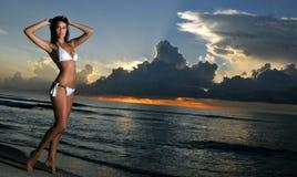 Het mooie donkerbruine model stellen op de oceaankust bij zonsopgang stock foto