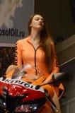 Het Mooie donkerbruine model van het Motopark 2015 in een oranje kostuum die een motorfiets berijden Royalty-vrije Stock Foto