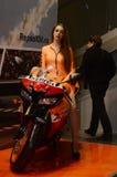 Het Mooie donkerbruine model van het Motopark 2015 in een oranje kostuum die een motorfiets berijden Royalty-vrije Stock Afbeelding