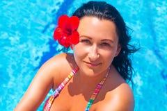 Het mooie donkerbruine ontspannen bij zwembad Royalty-vrije Stock Afbeeldingen