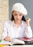 Mooi studentenmeisje dat een baret draagt. Stock Foto's