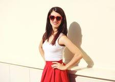 Het mooie donkerbruine vrouw dragen zonnebril en rode rok in stad Stock Foto's