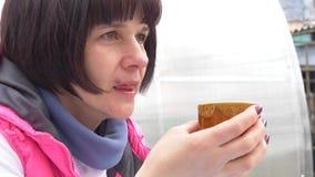 Het mooie donkerbruine vrouw drinken van een kop stock footage