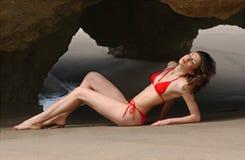 Het mooie donkerbruine vrouw stellen bij het strand in rode bikini Royalty-vrije Stock Afbeelding