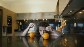 Het mooie droevige meisje spelen met sinaasappelen op lijst stock video