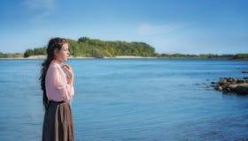 Het mooie eenzame meisje bevindt zich in de rivier stock afbeelding