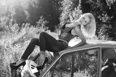 Het mooie, elegante, sexy meisjesblonde in jeans in zwarte schoenen zit op de oude auto in het bos Stock Foto's