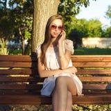 Het mooie emotionele donkerbruine meisje lachen op de telefoon in de de glazen roze kleding van de parkzomer, geniet van uw vakan Stock Foto's