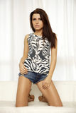 Het mooie en aantrekkelijke donkerbruine vrouw stellen in jeans dre Royalty-vrije Stock Foto