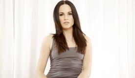 Het mooie en aantrekkelijke vrouwelijke vrouw stellen in grijs overhemd op Th Royalty-vrije Stock Foto's
