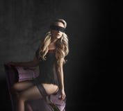 Het mooie en jonge vrouw stellen in sexy lingerie en kousen Stock Foto's