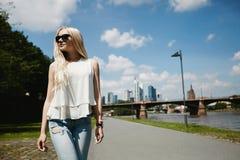 Het mooie en leuke blonde modelmeisje in modieuze zonnebril, in witte blouse en jeans bekijkt kant en loopt langs de promenade stock afbeelding