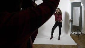 Het mooie en model die stelt voor een jonge fotograaf met donker haar in een professionele studio in langzame motie slaan glimlac stock footage