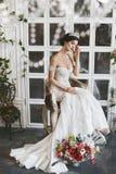 Het mooie en modieuze donkerbruine modelmeisje in modieuze huwelijkskleding met naakte schouders en met diadeem op haar hoofd zit stock afbeeldingen