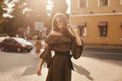 Het mooie en modieuze donkerbruine modelmeisje in modieuze kleding met naakte schouders en in de in zonnebril glimlacht en stelle royalty-vrije stock afbeelding