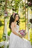 Het mooie en sensuele donkerbruine modelmeisje met heldere make-up en met boeket van bloemen in haar dient witte kantkleding in z Stock Foto