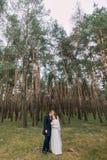 Het mooie enkel echtpaar kussen in groen naaldboomhout Het openluchtportret van gemiddelde lengte Stock Foto's